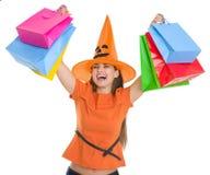 上升购物袋的万圣节帽子的女孩 免版税库存照片
