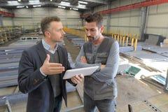 上司和工作者交谈的在工厂 库存图片
