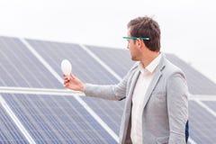 上司在他的手和神色上拿着一个电灯泡在它以太阳电池板为背景 免版税库存照片