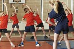 上在学校健身房的老师锻炼课 免版税库存图片