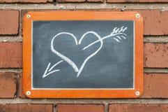 上在有心脏的一个砖墙上与箭头 免版税库存照片