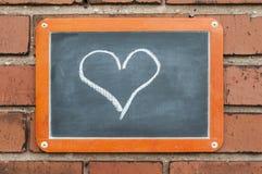 上在有心脏的一个砖墙上 免版税图库摄影