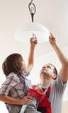 登上天花板灯的男孩帮助的父亲-拧紧在lig 库存照片