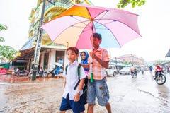 上学的高棉学生在一个雨天 戈公省 免版税图库摄影