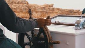 上尉在岩石附近控制在海风暴的旅游游艇 游船的方向盘 影视素材