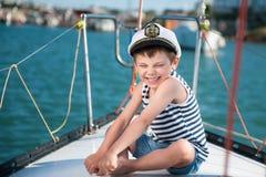 上尉帽子的逗人喜爱的愉快的令人愉快的小男孩在夏天巡航的游艇板 免版税库存图片
