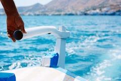 上尉的手在海岛克利特附近控制在一条木小船的船舵引擎在海 概念的可靠和 库存图片