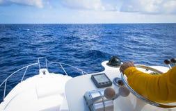 上尉的手汽船方向盘的在交付蓝色的海洋渔场天 免版税图库摄影