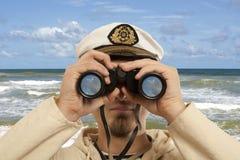 上尉通过看双筒望远镜 库存图片