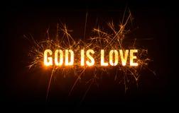 上帝是在黑暗的背景的爱标题 免版税库存照片