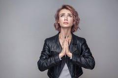 上帝,请原谅我 哀伤的祷告美女画象有短的发型和构成的在便装样式黑皮夹克 免版税库存图片