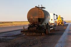 上油应用表面上的分布器卡车粘结层为准备铺 库存图片