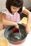 上油模子的愉快的小女孩烘烤蛋糕 库存图片