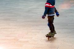 上海中国, 2017年11月3日:滑板的一个男孩与手和膝盖保护 库存图片