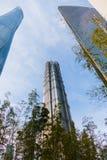 上海,中国- 2018年1月15日:云彩被反射的一个高玻璃摩天大楼 附近有树 库存照片
