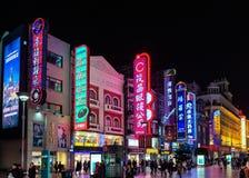 上海,中国- 2019年3月12日-夜景观点的霓虹灯、顾客和步行者沿南京东路南京 图库摄影