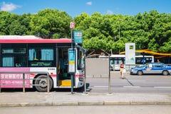 上海,中国- 2016年8月8日:桃红色公共汽车和出租汽车在公共汽车站 库存图片