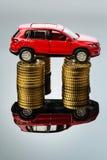 上涨的开汽车的费用。在硬币的汽车 免版税库存图片