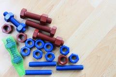 上漆的螺柱螺栓和坚果在木纹理 库存图片