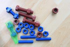 上漆的螺柱螺栓和坚果在木纹理 免版税库存照片