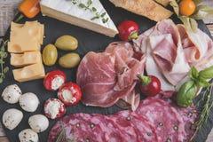 上用熏火腿、蒜味咸腊肠、烟肉和乳酪无盐干酪,咸味干乳酪,橄榄,腌汁 库存照片