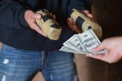 上瘾者人的手有金钱可卡因或女英雄购买药量的,关闭从毒贩的上瘾者买的药量,毒品交易 免版税图库摄影