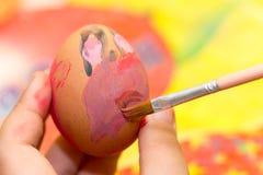 上色与刷子和蛋彩画的儿童的手复活节彩蛋 库存图片
