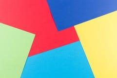 上色与黄色,绿色,红色和蓝色口气的纸几何平的构成背景 免版税库存照片