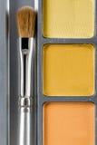 上色化妆用品不同的眼影膏专业 黄色眼影和构成刷子,顶视图调色板  库存照片