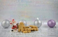 上色圣诞节食物摄影姜饼人圣诞老人和在xmas包装纸背景的银紫色树中看不中用的物品 免版税图库摄影