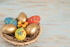 上色在一个篮子的复活节彩蛋与黄色婴孩鸡复活节概念 图库摄影