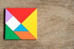 上色在方形的形状的七巧板难题在木背景 免版税库存照片