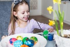 上色复活节彩蛋的微笑的小女孩 免版税库存图片