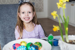 上色复活节彩蛋的微笑的小女孩 库存照片