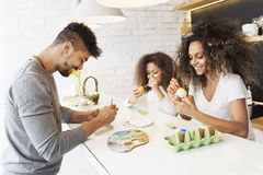 上色复活节彩蛋的愉快的非裔美国人的家庭 免版税库存照片