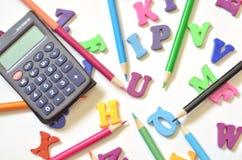 上色英语字母表的信件,色的铅笔,计算器 顶视图 教的孩子 图库摄影