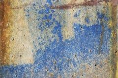 上色被毁坏的在难看的东西的混凝土和蓝色的明亮的纹理与出现的铁锈的 库存照片