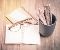 上色铅笔由与玻璃和笔记本的分支做成在木头 库存图片
