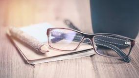 上色铅笔由与玻璃和笔记本的分支做成在木头 免版税库存照片