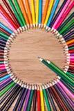 上色铅笔被安排在木背景,顶视图的一个圈子 库存图片