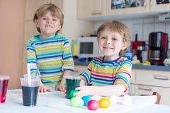 上色鸡蛋的两个小白肤金发的孩子男孩为复活节假日 免版税图库摄影