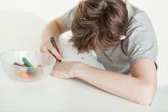 上色他的图画的年轻男孩使用蜡笔 免版税库存照片
