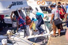 上轮渡或游览小船的游人 免版税库存照片