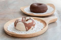 上釉圆环用在木盘子的巧克力在桌上 免版税库存照片