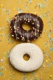 给上釉的油炸圈饼用在金背景的巧克力 免版税库存图片