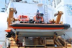 登上阿西西海岸卫队刚性可膨胀的小船今后美国海岸卫队切削刀 库存照片