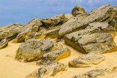 上面一个与它的许多洞的红砂岩和可看见的侵蚀在多云天空下 免版税库存照片
