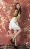 上面和裙子和平台凉鞋的年轻长发长腿的皮包骨头的女孩 免版税库存照片