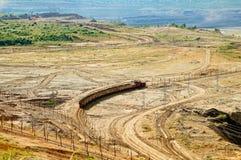 上面曝露的矿,运载被挖掘的材料的开采的火车 采矿机在背景中 图库摄影