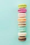 从上面结块macaron或蛋白杏仁饼干在蓝色背景 五颜六色的杏仁饼干 背景看板卡问候页模板通用葡萄酒万维网 平的位置 免版税库存图片